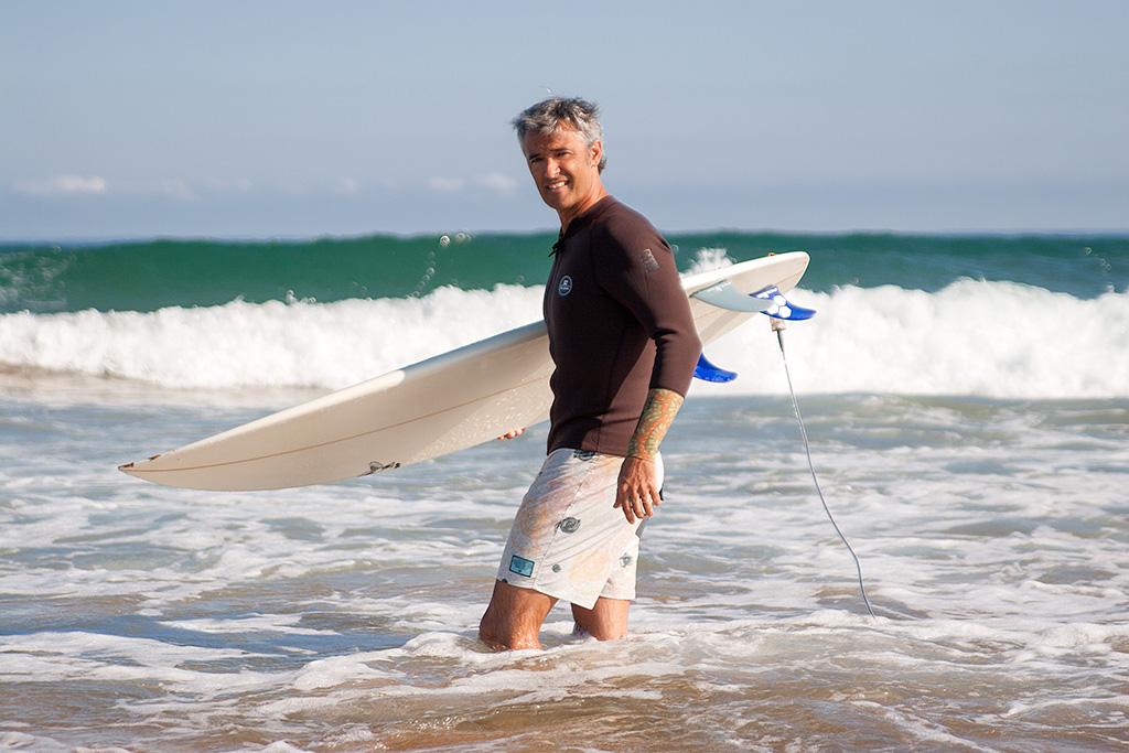 Angel Unzueta haciendo surf en la playa de Zarautz con prendas de PUKAS.