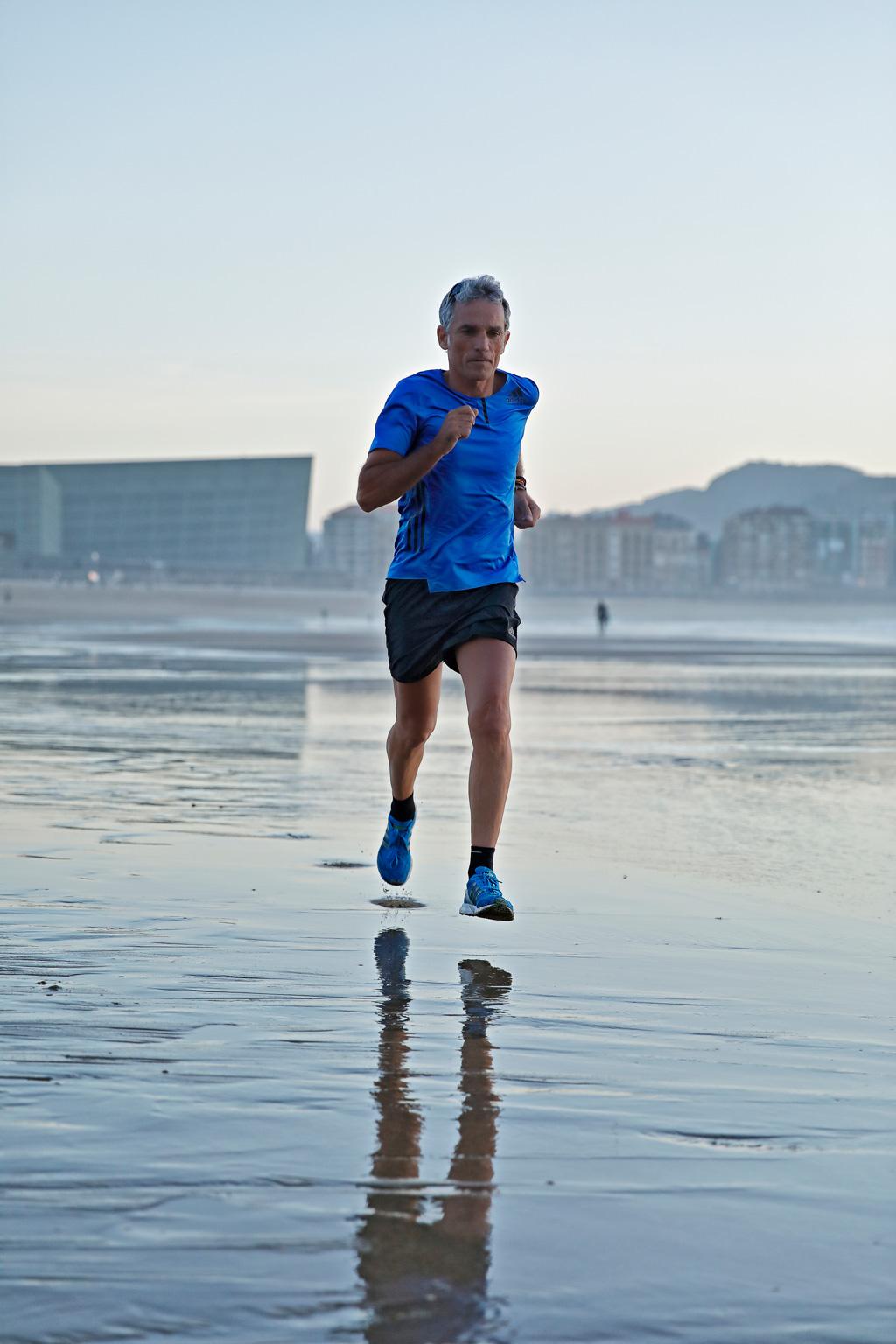 Javier Colomo de AMISOLIDARIOS corriendo por la playa de La Zurriola con prendas de la tienda deportiva ROBERS.